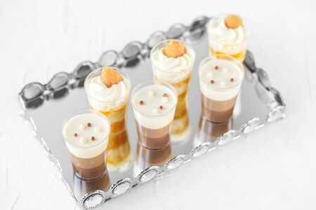 Set of delicious cream desserts on a tray.