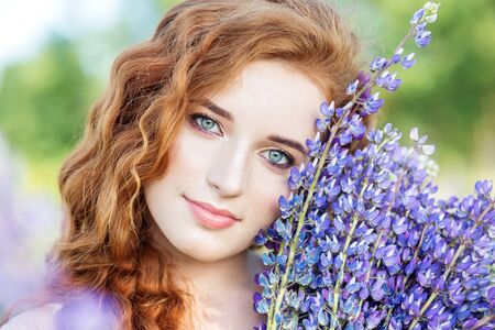 Red-haired curly woman holds lupine flowers. Close-up. Concept slow life, organic cosmetics and digital detox.