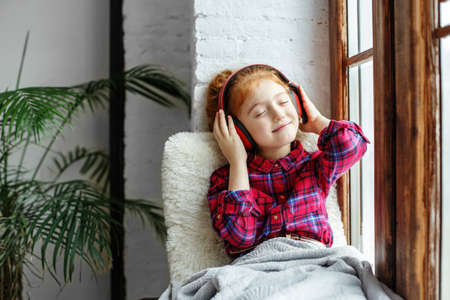 A teenage girl with red curly hair enjoys listening to music sitting on the windowsill. Listen to music school girl Фото со стока
