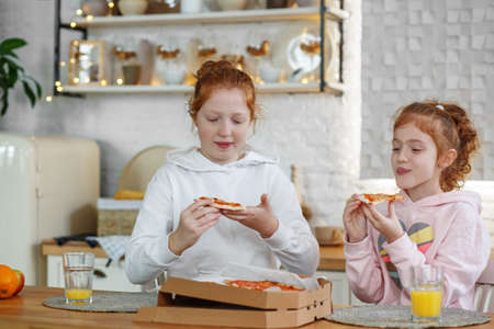 Young girls with red hair in the kitchen eating pizza, drinking juice.