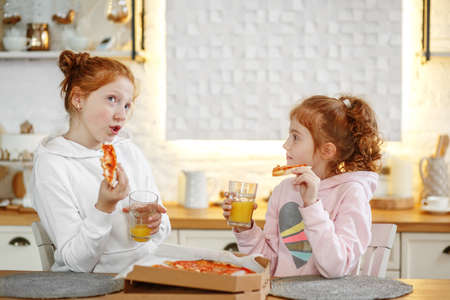 Young girls with red hair in the kitchen eating pizza