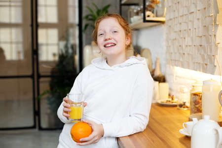 Young girl with red curly hair drinks orange juice standing in the kitchen Фото со стока