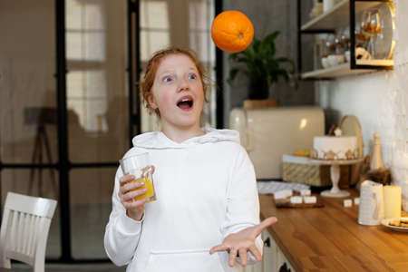 Young girl with red hair, teenager, in a modern kitchen playing with an orange, drinking orange juice, happy. Фото со стока