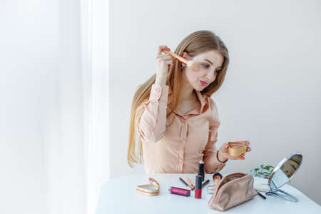 A girl in a pastel-colored blouse is sitting at a makeup table, holding makeup brushes and making up, smiling mysteriously. Фото со стока