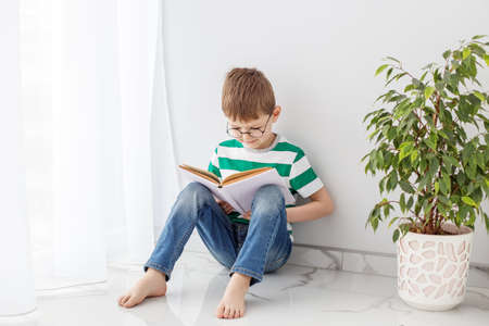 A boy in a green striped T-shirt sits on the floor enthusiastically reading a book, spends his leisure time studying, next to a green tree. Фото со стока