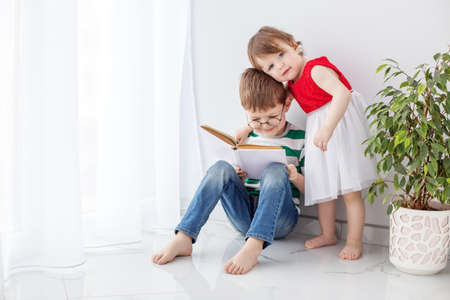 Little boy and girl spend their leisure time together, reading a book, in a bright room next to a house plant.