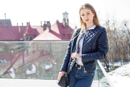 A young girl in a dark leather jacket in the spring sun, walking around the city.