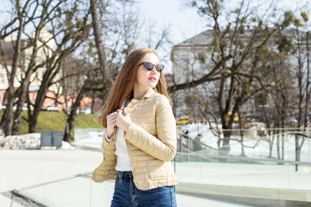 A beautiful blonde girl in a short light jacket and sunglasses walks around the city, enjoying the spring weather.