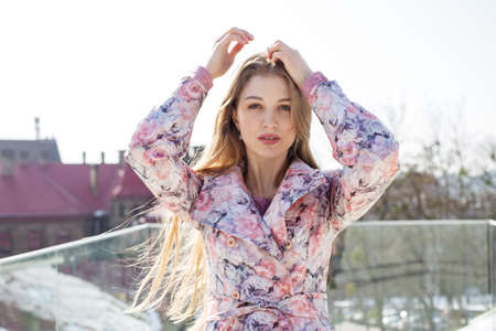 Girl with long hair in a floral print coat, fluttering in the wind, walking around the city.