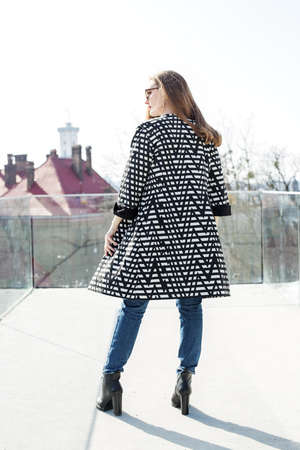 A woman in a long plaid coat stands on the street with her back turned. Фото со стока