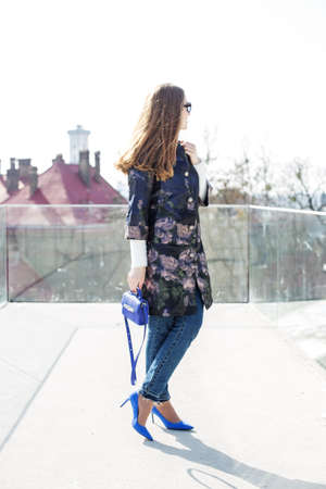 Feminine girl in a blue coat and bag walks around the city, sunny weather.