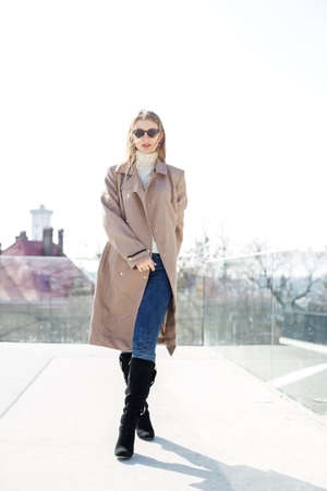 Young girl wearing sunglasses with long blonde hair in the wind, wearing a long coat outside.