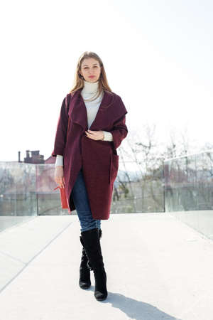 A woman in a purple coat with three-quarter sleeves in high boots on a city street. Фото со стока