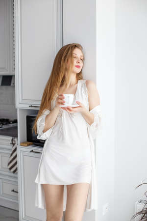 A beautiful girl with long hair enjoys a morning coffee or tea in her modern kitchen.