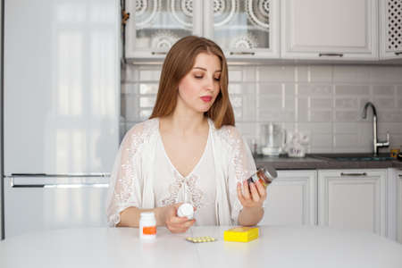 The girl sitting at the table reads the recipe, the composition of vitamins, medicines, dietary supplements.