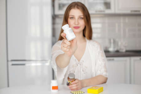 A beautiful woman in white clothes points to a tube of medication, vitamins or dietary supplements. Фото со стока