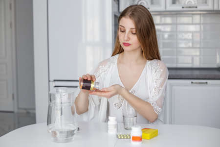 Young beautiful girl takes vitamins in the morning in her kitchen, pours water from a pitcher.