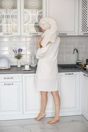 A young girl in a white robe and with a towel on her head stands in a white kitchen. Фото со стока
