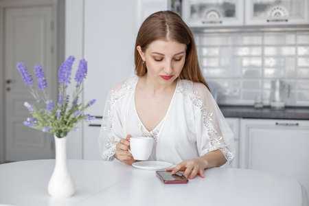 A young beautiful girl sits at a white table in the kitchen and looks at the phone, reads the morning news over a cup of coffee. Фото со стока