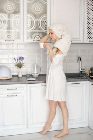 A young girl in a white robe and with a towel on her head is standing in a white kitchen, holding a cup of tea and coffee. Morning ritual. Фото со стока