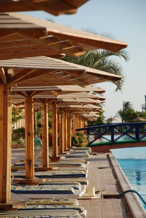 Plank beds under umbrellas at pool in hotel. Egypt Stock Photo - 11729924