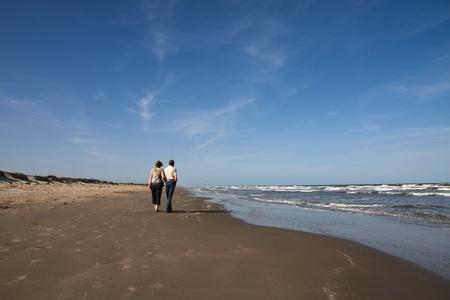 Senior couple walking on a beach photo