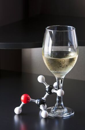 tipsy: Glass of cold wine and a tipsy ethanol molecule