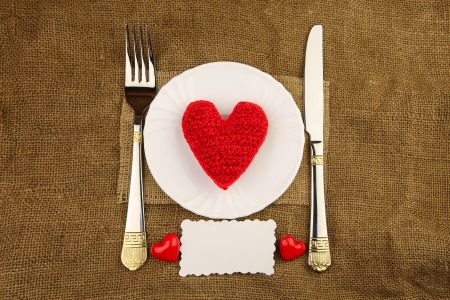 Valentine s dinner with handmade heart on the white plate with sacking background photo