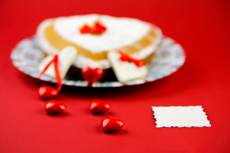 baker's: Cake ond little red hearts on the red background with the place for the sample text
