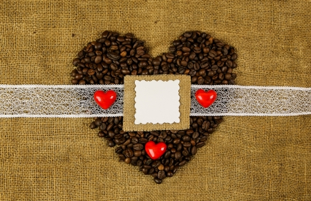 Big  heart of coffee beans with little hearts on the sackcloth background with the place for text photo