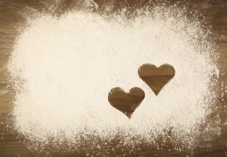 White flour on the table with drawing hearts photo