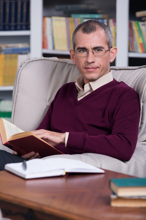 Handsome successful lawyer reading a book in his office