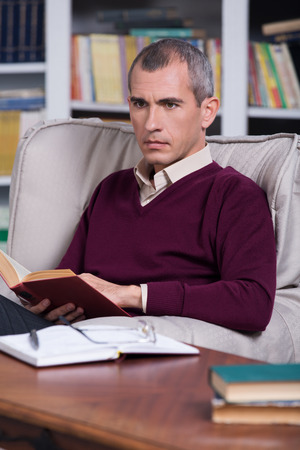 sociologist: Handsome successful lawyer reading a book in his office Stock Photo