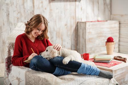 persona escribiendo: Mujer joven con su animal doméstico, golden retriever, relajarse juntos
