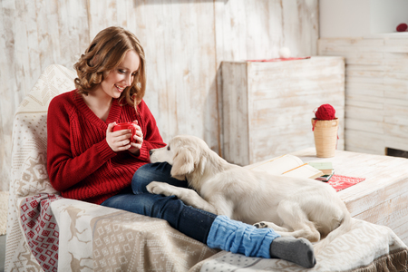 Young woman with her pet, golden retriever, relaxing together