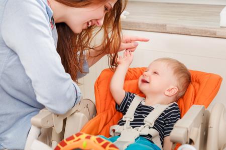padres hablando con hijos: joven madre jugando con su bebé en casa