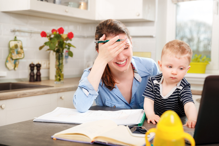 a young baby: Young mother working with her baby at home