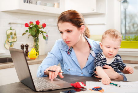 people working together: Young mother working with her baby at home