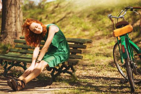 bicyclette: Jeune femme rouge-cheveux sont des si�ges sur le banc avec r�tro bicyclette dans le parc