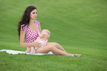 Young woman breastfeeding her baby outdoors at summer