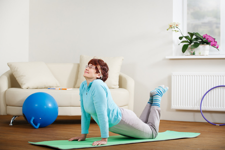 Happy senior woman doing yoga at home