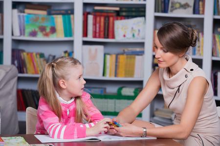 El psicólogo infantil con una niña, un niño dibuja con lápices de colores