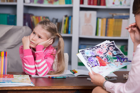 Child psychologist working with little girl's pictures Standard-Bild