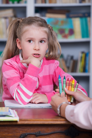Little girl chooses the color pencils with hand psychologist Stock Photo