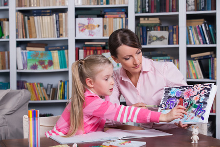 Child psychologist working with little girls pictures Stock Photo