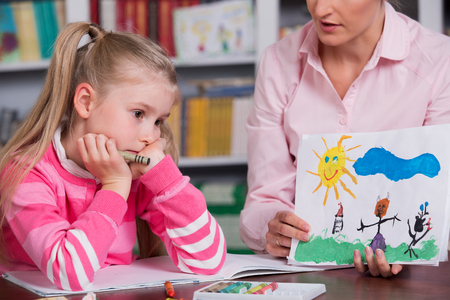 psicologia: El psicólogo infantil con una niña triste, el médico observa la imagen del niño