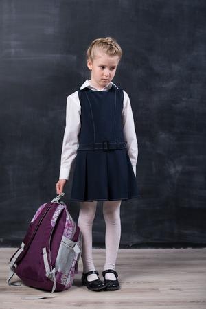 Retardataires petite écolière avec sac à dos près de tableau noir