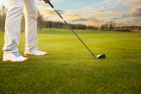 Golf ball on grass in front of golf club