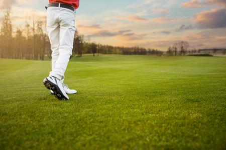 Legs of boy golf player on fairway