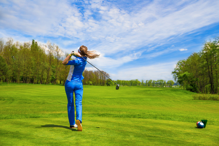 Woman golf player hitting by iron from fairway